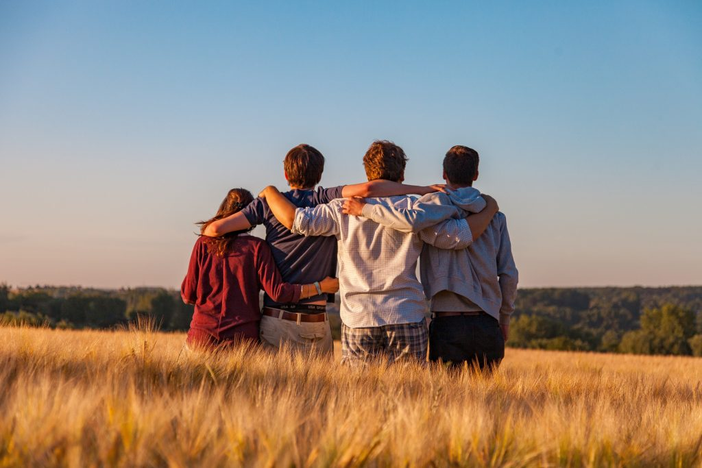 Four young people, their arms on each others' shoulders and with their backs to the camera, standing in a field and looking out at the horizon.