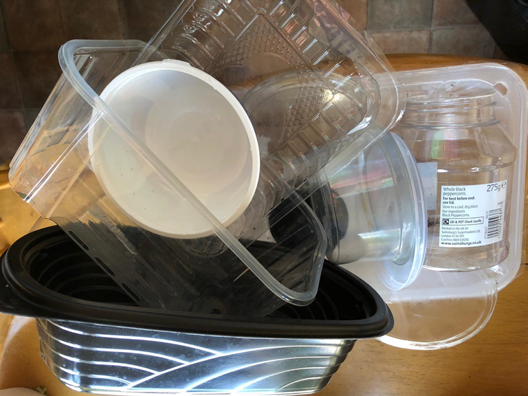 Empty plastic trays and tubs for recycling