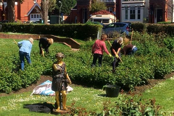 Volunteers at work in the rose garden.