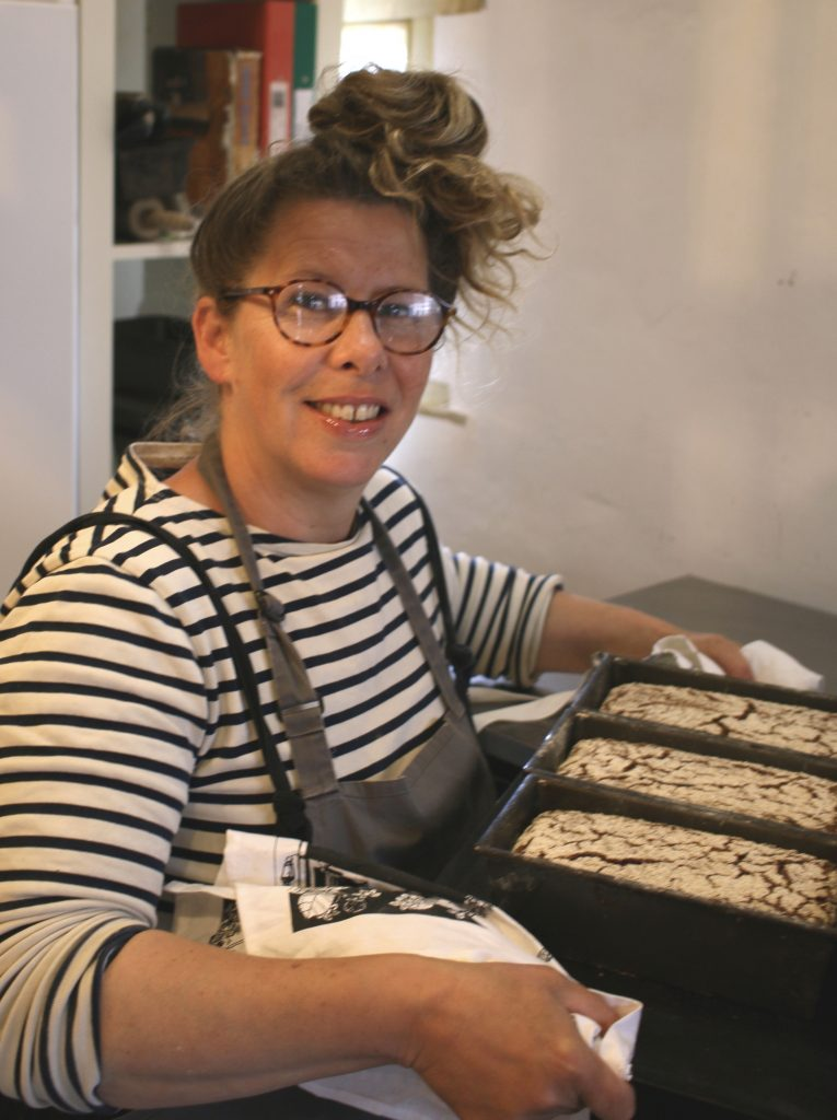 The author Paula with three loaves in tins just out of the oven