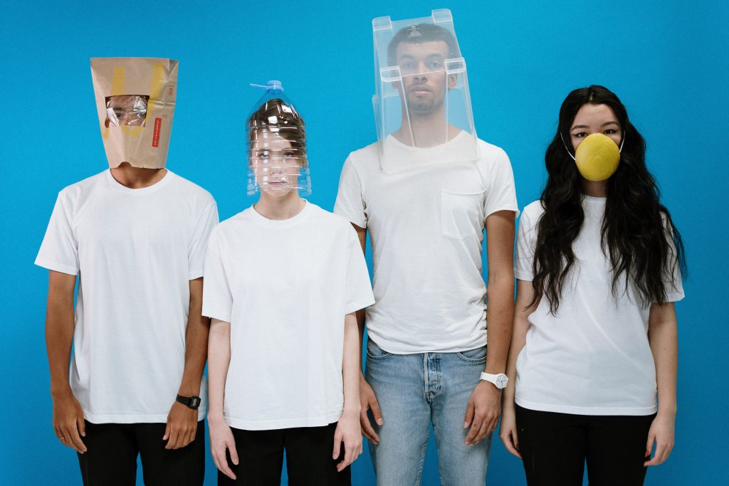 Four young people with bizarre coverings over their heads - illustraing the irony of banning any kind of face coverings during the Covid pandemic