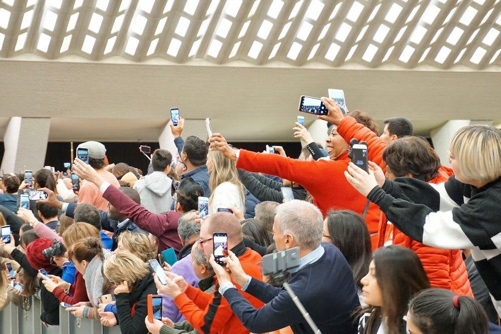 People all using their mobile phones to photograph something.