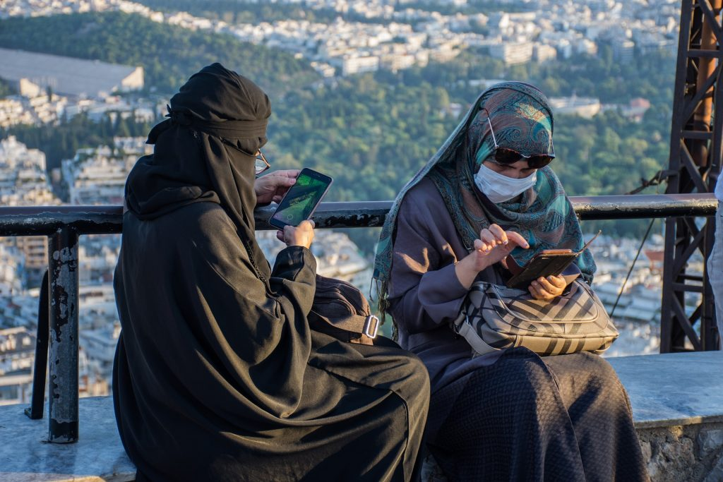 Two young Muslim women wearing headscarves and Covid facemasks while looking at their smart phones