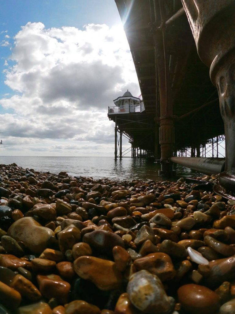 Shot of Brighton Palace Pier, looking up from the pebbled beach to the iron structure and a small pavilion on the eastern side of the pier.
