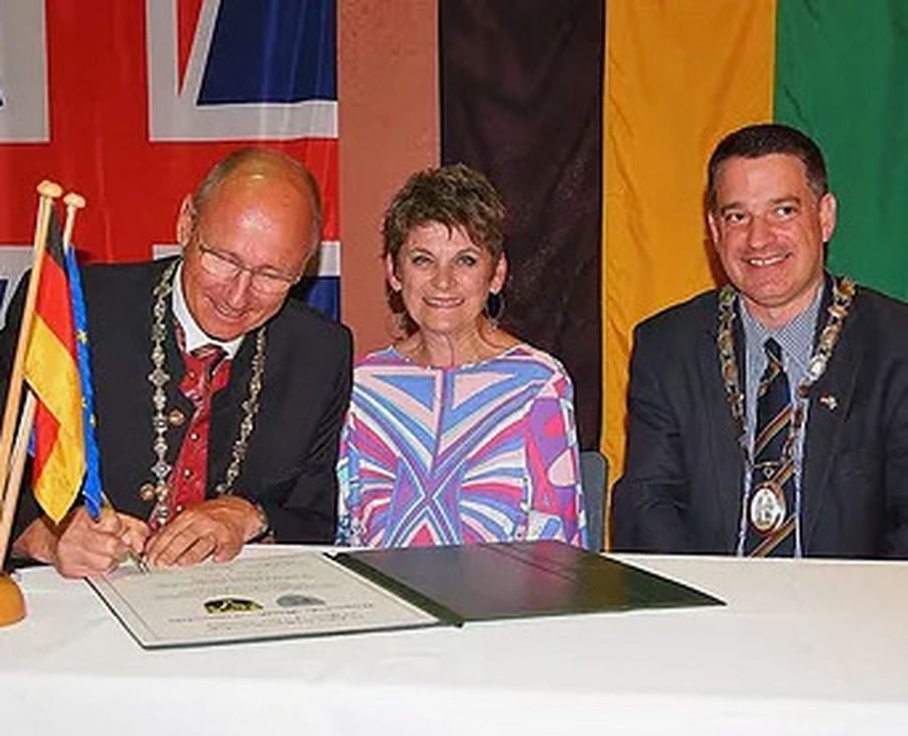 Flanked by flags, the mayor of a Bargain town signs a twinning document. Alongside him are the major of Haywards Heath and the twinning association chair Irene Balls