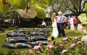 A satirical photo tableau depicting Boris Johnson and new bride Carrie Symonds in the rose garden with body bags piled high