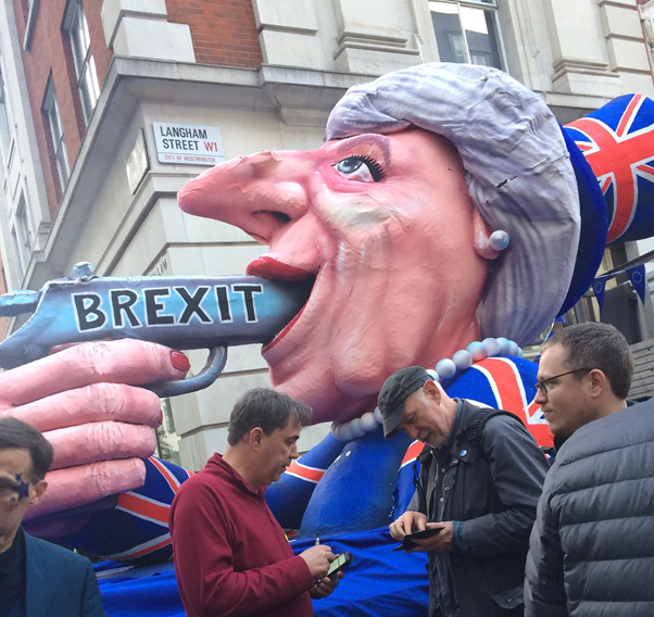 Large papermache sculpture of former prime minister Theresa May, pointing a gun labelled 'Brexit' into her mouth.
