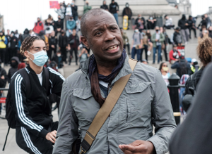 Photo of Clive Myrie, with Black Lives Matter protestors in the background