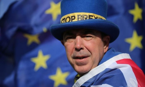 Steven Bray wearing a blue top hat with a yellow and black 'Stop Brexit' ribbon. He has a Union flag draped around his shoulders and an EU flag in the background.