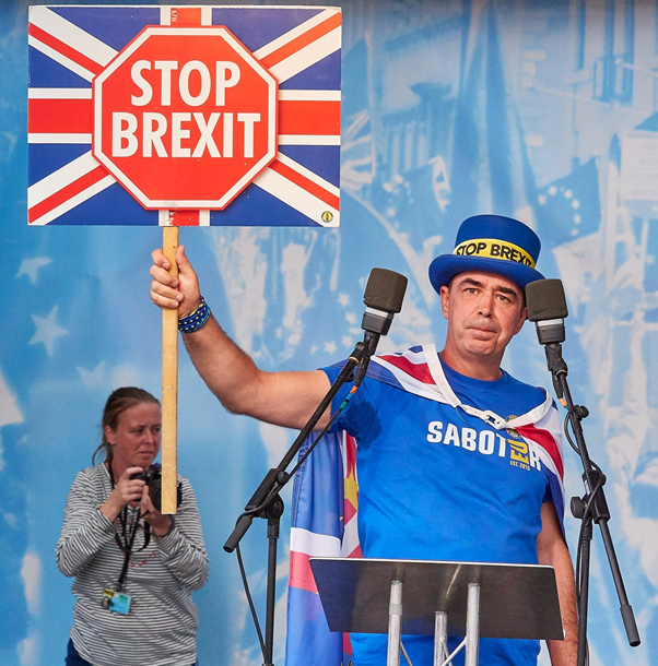 Steven Bray at a podium giving a speech and holding up a 'Stop Brexit' placard. In the background a photographer taking pictures.