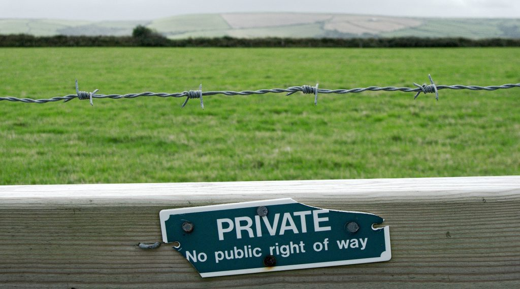 """Sign reading """"Private - No public right of way"""" on fence with barbed wire with open countryside behind it"""