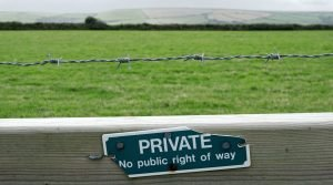 Private property sign on a barbed wire fence in the UK countryside