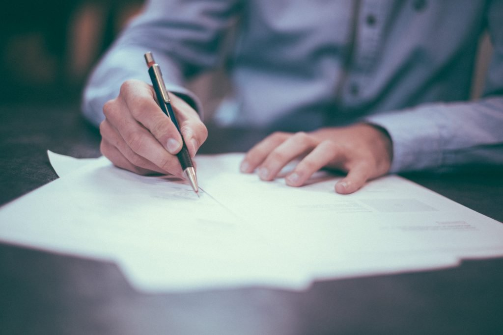 Picture of man's hands at a desk as he checks out some paperwork