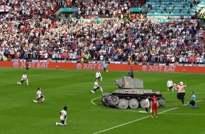 Image showing the England football team kneeling on the pitch with Priti Patel arriving in a tank and Boris Johnson streaking topless