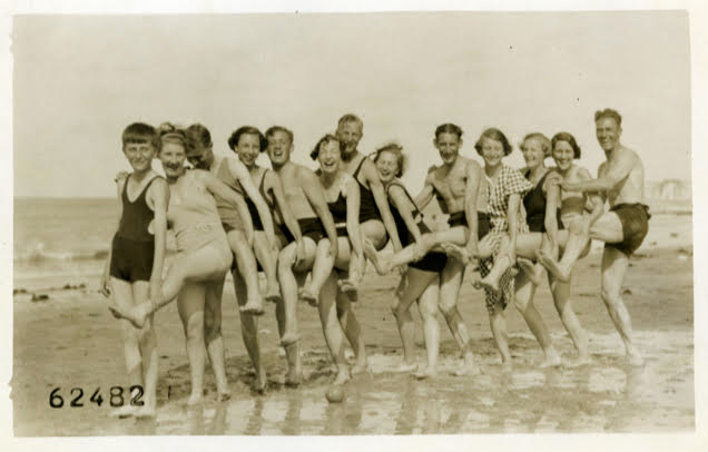 A photo of happy holidaymakers frolicking and posing for the camera on a Kent beach in the fifties