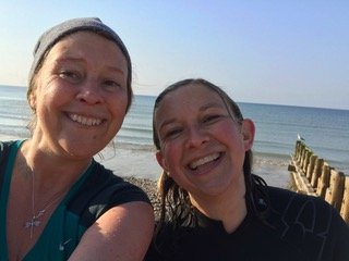 Author Louise Serpell and her sister Lucy smiling after their dip in the sea