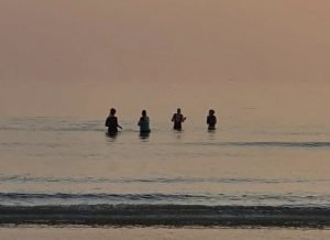 Cold water swimmers in the sea at sunrise, Brighton