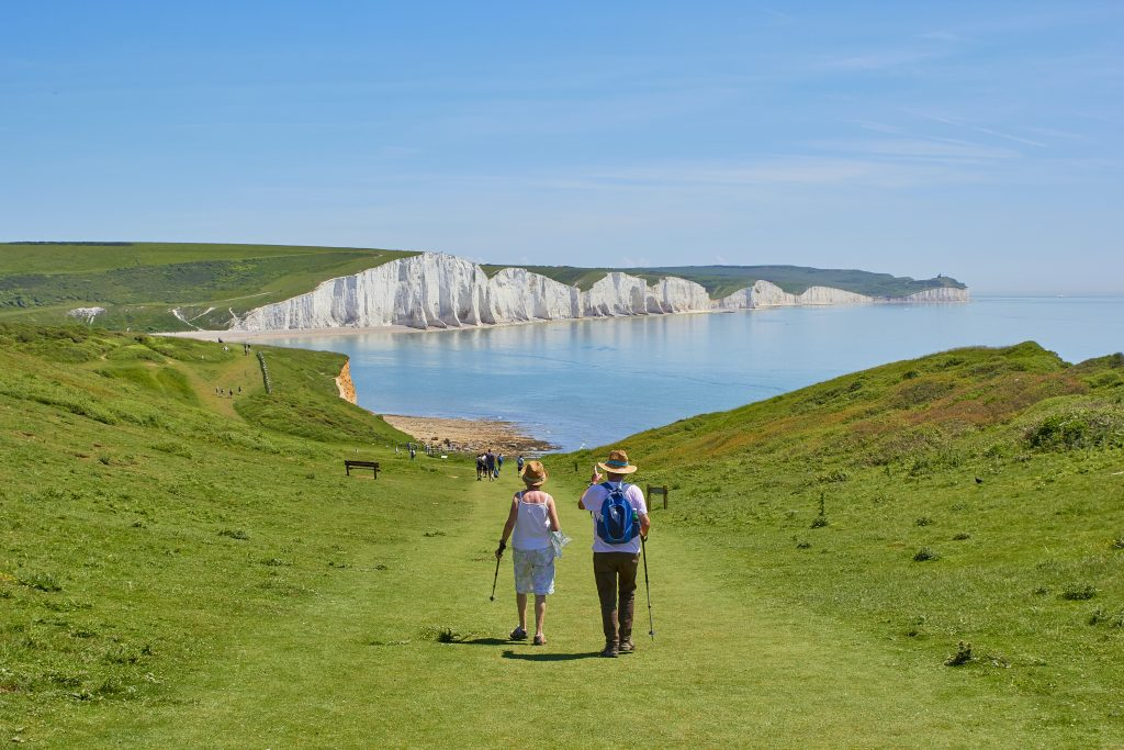 Walkers at Seven Sisters near Eastbourne, where the green grass of the South Downs meets the blue of the sea and the white of the chalk cliffs