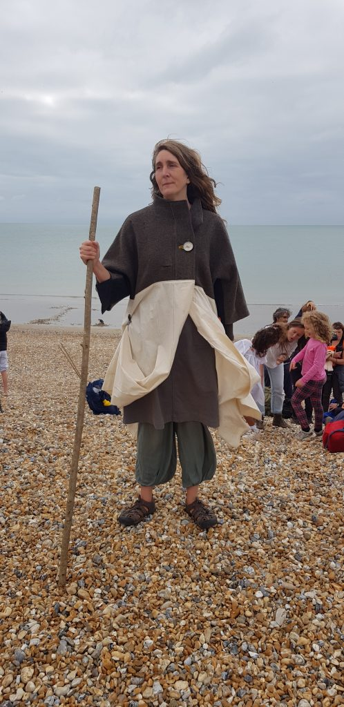 Coat of Hopes founder Barbara Keal standing on Newhaven Beach wearing the coat and carrying a staff