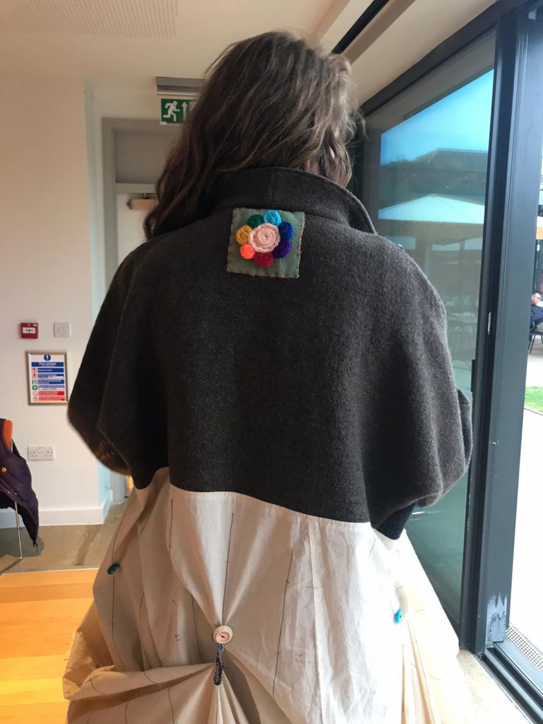 The back of the Coat of Hopes worn by Barbara Keal showing the first colourful patch that was sewn on in Sussex