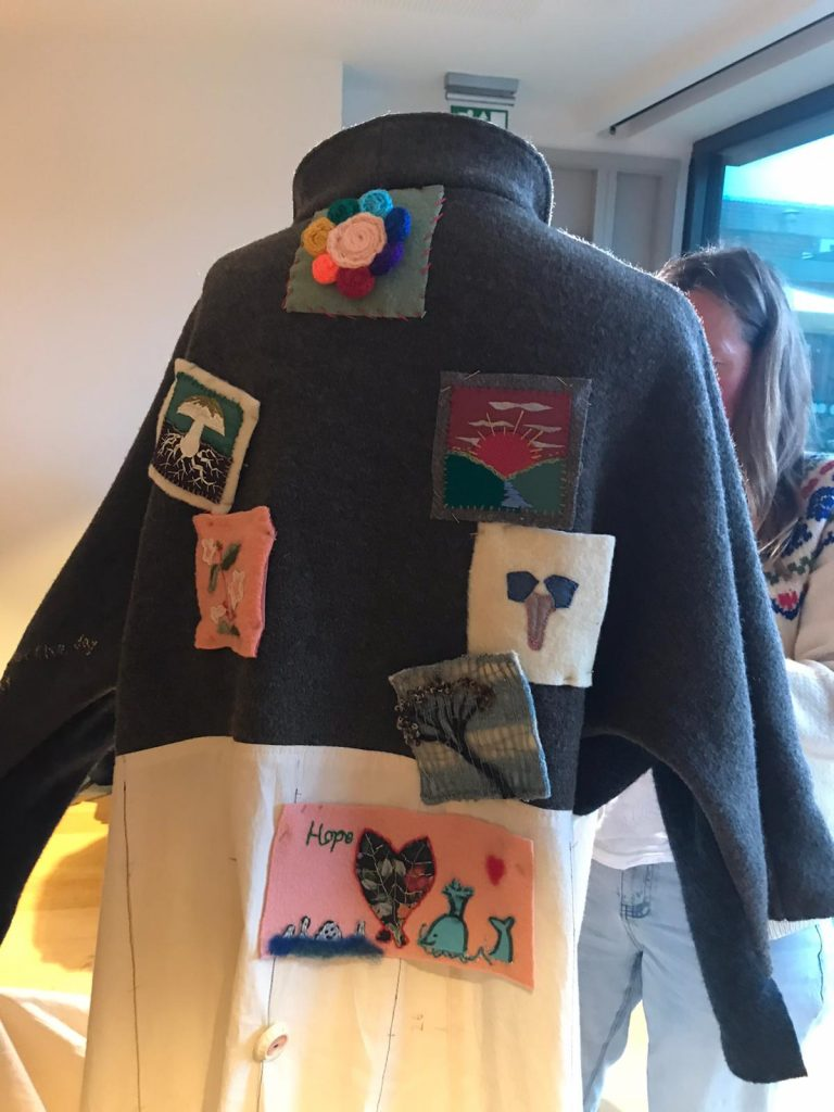 The back of the Coat of Hopes with the first batch of patchwork squares being sewn on in Lewes, East Sussex
