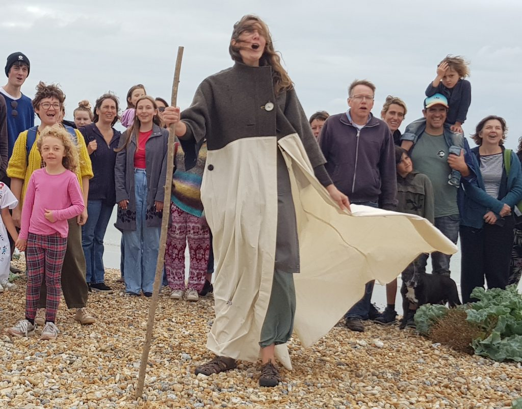 Barbara Keal standing on Newhaven beach wearing the as-yet unadorned Coat of Hopes and leading a group in song