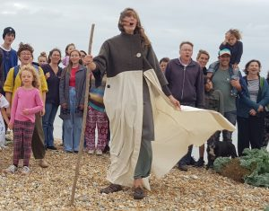 Barbara Teal wearing the Coat of Hopes before any patches have been added, leading a group in song on Newhaven Beach
