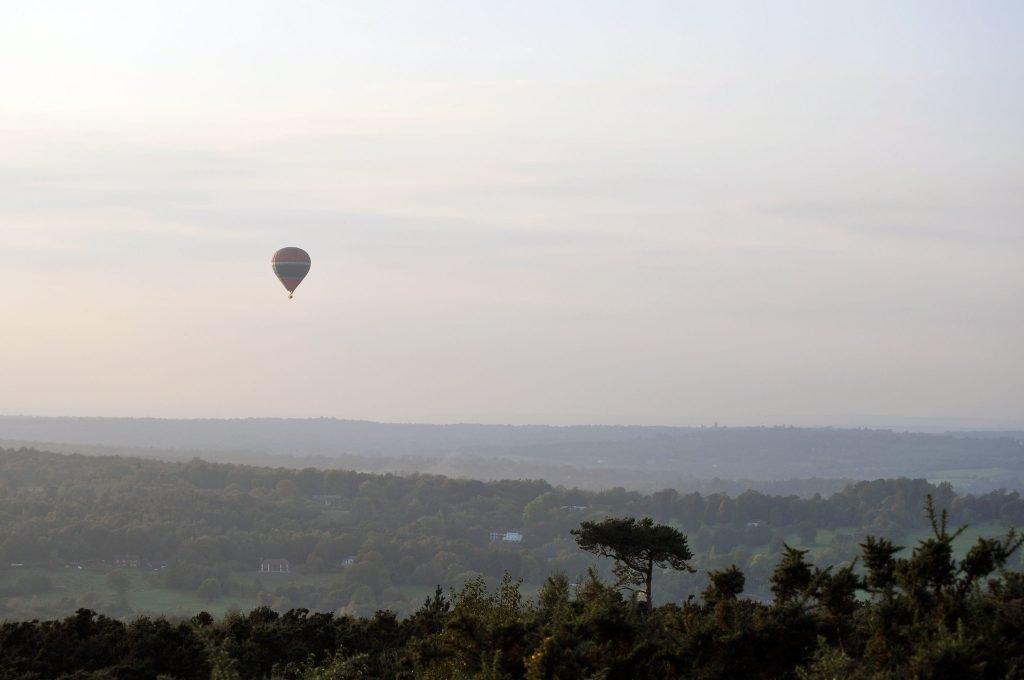 A hot air balloon floats over the Ashdown Forest