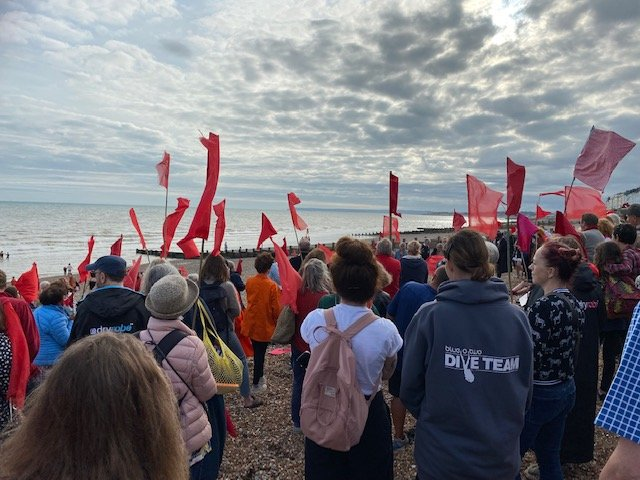 Protestors holding red flags on a Hastings beach following another recent Southern Water sewage discharge