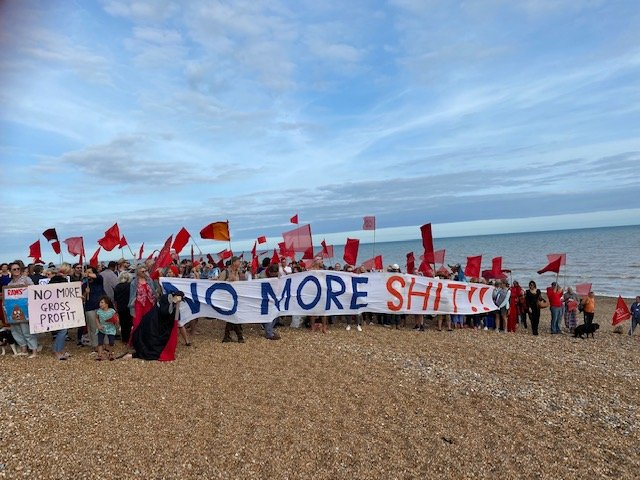 """Protestors on a Hastings beach holding homemade signs that read """"No more Shit!!"""" and """"No more Gross profit!"""""""