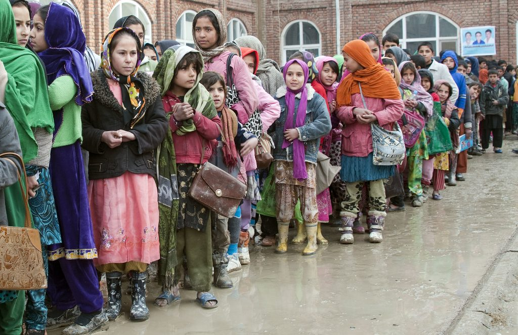 Afghan refugee children in Kabul line up to receive donations of winter clothing