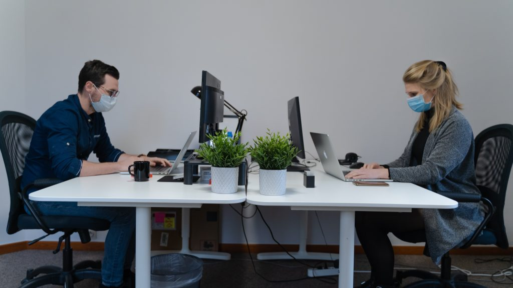 A man and woman in masks work on their computers in an office