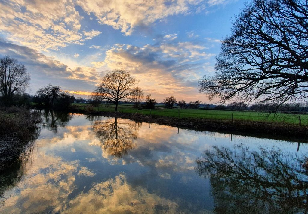 Evening scene on the Ouse. Clouds are reflected in the still water of the river.