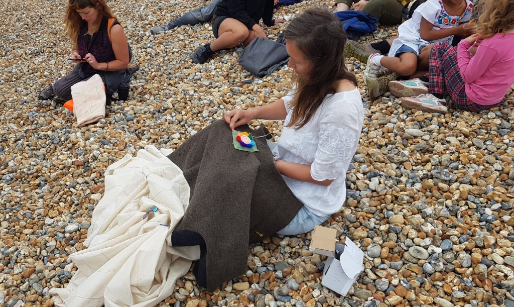 A woman sits on the shingled beach and sews the first patchwork square onto the Coat of Hope