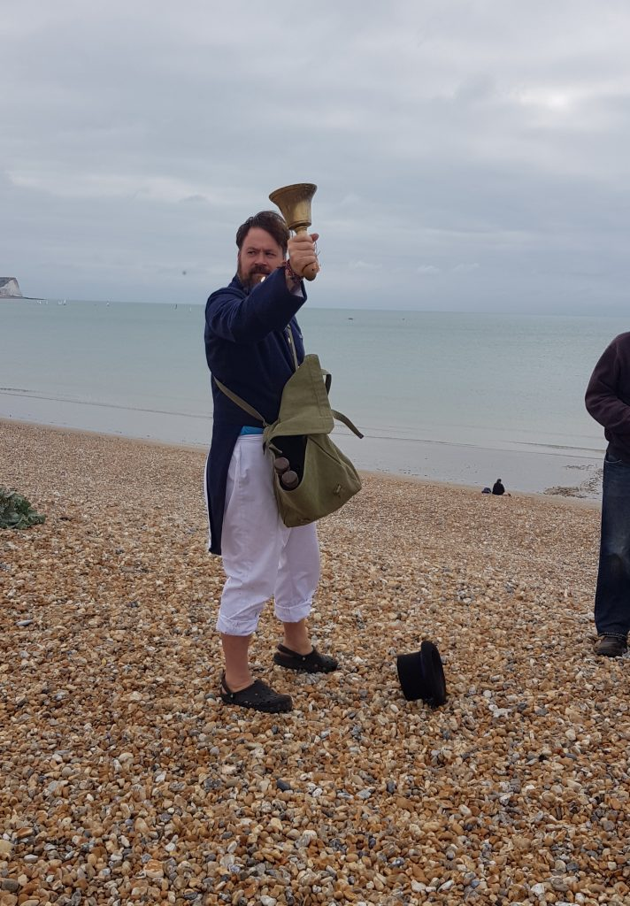 A town crier ringing his bell on the shingled beach in Newhaven, East Sussex