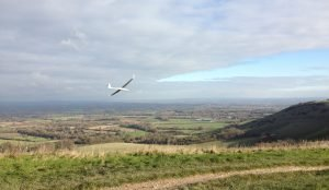 A glider flies over the South Downs near Ditchling Beacon, East Sussex