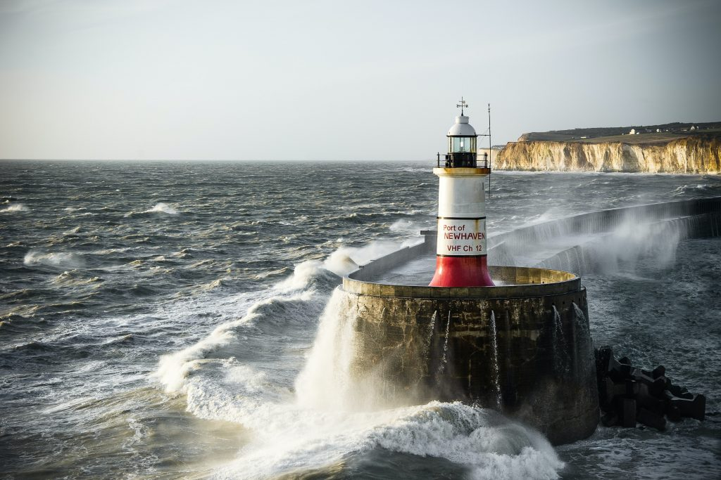 Newhaven Lighthouse with waves crashing into it