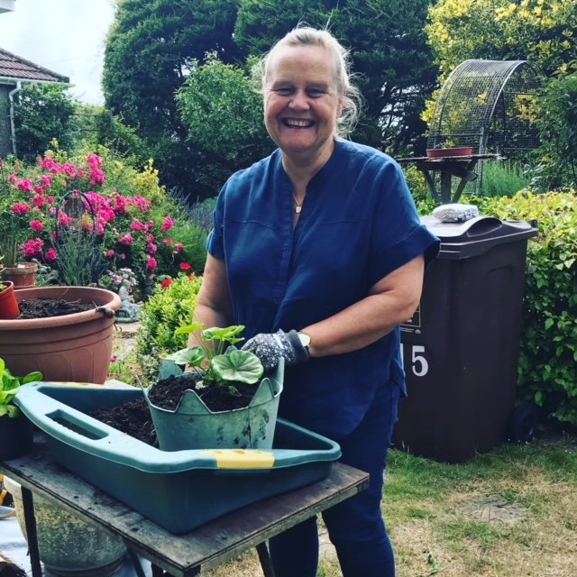 A smiling volunteer with potted plant in very productive looking garden, trees and red flowers in the background