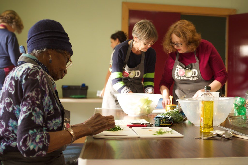 A cookery group concentrating on their tasks. In the foreground a woman pauses from chopping vegetables, and behind her two women work together, also preparing ingredients.
