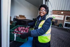 Fare share volunteer loading donated surplus onions in a crate into a van for distribution to the community