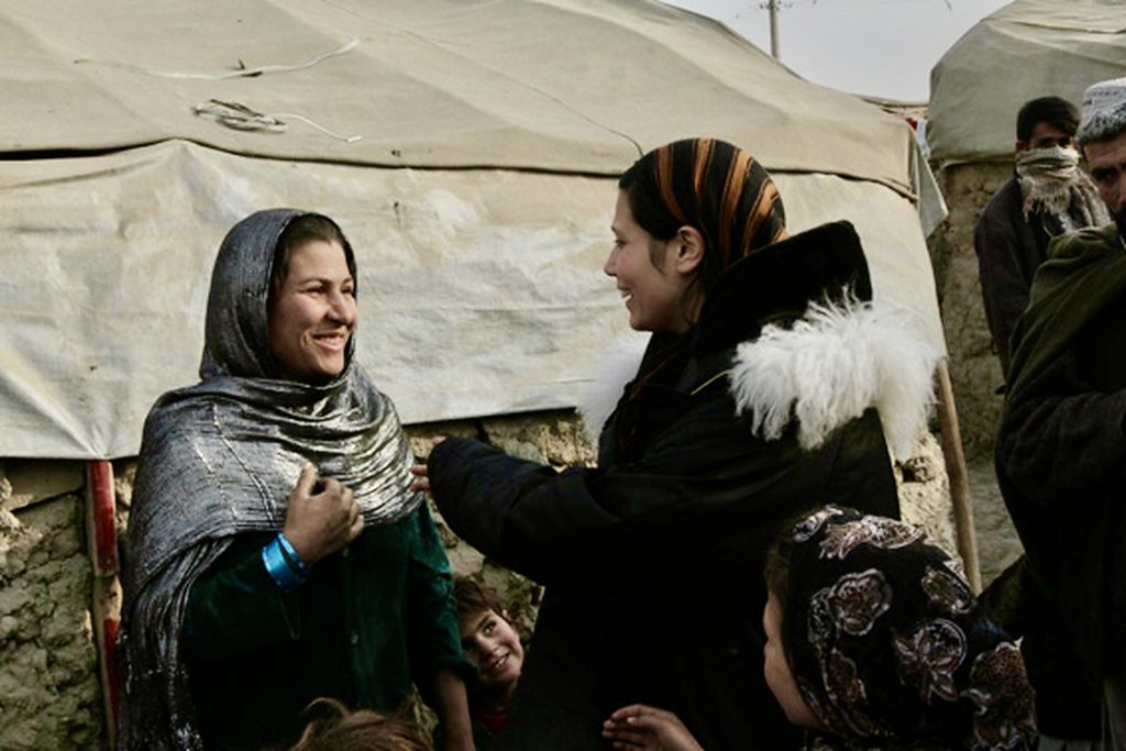 The author talks to a smiling woman in a refugee camp