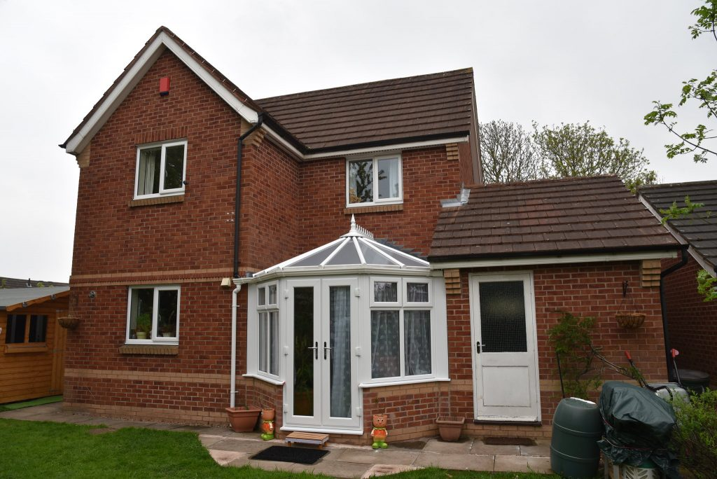 A modern British house with a tiny faux Victorian conservatory on the back