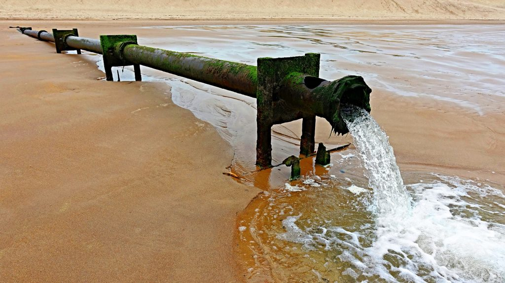 An outflow pipe spews water onto a beach.