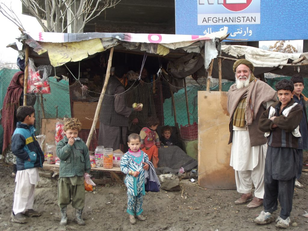 A smiling beaded older man and grow of children stand outside a makeshift shelter in a refugee camp