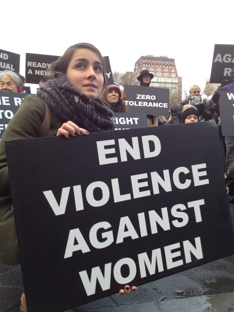 A female protestor at a rally with a sign that says End Violence Against Women