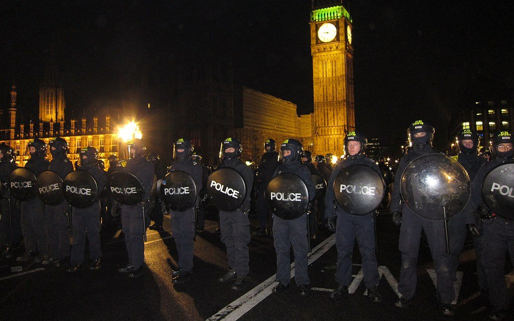 Riot police form a barrier with shields on Westminster Bridge in front of the Houses of Parliament at night